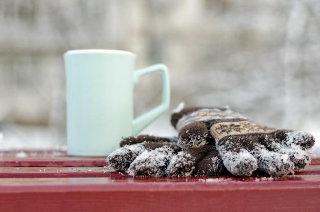 Niebieski kubek i damskie dzianinowe rękawiczki na ławce w zimę. zbliżenie