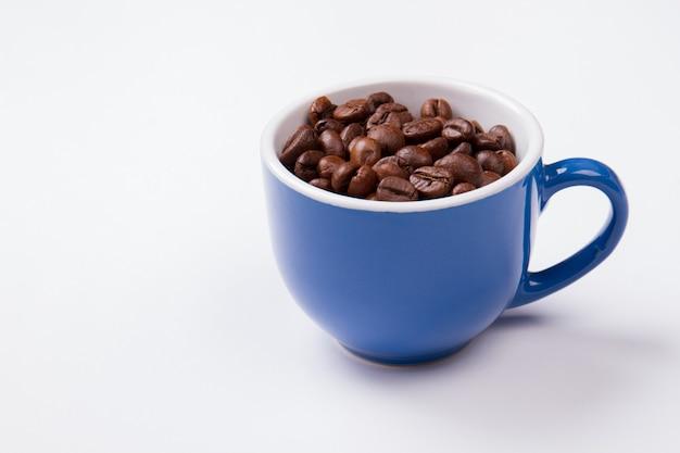 Niebieski kubek pełen ziaren kawy na białym tle