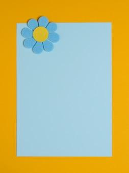 Niebieski kwiat wykonany z filcu na niebieskim i pomarańczowym tle.
