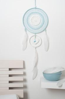 Niebieski łapacz snów z białymi piórami