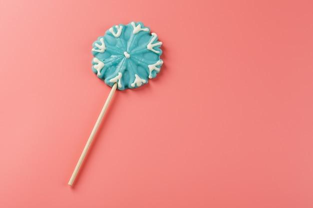 Niebieski lollipop w kształcie płatka śniegu na różowym tle. słodki lizak cukrowy. minimalna płaska kompozycja płaska, wolna przestrzeń