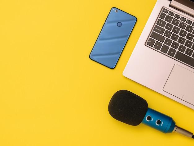 Niebieski mikrofon niebieski smartfon i laptop przy żółtym stole. pojęcie organizacji miejsca pracy. sprzęt do nagrywania, komunikacji i słuchania muzyki.