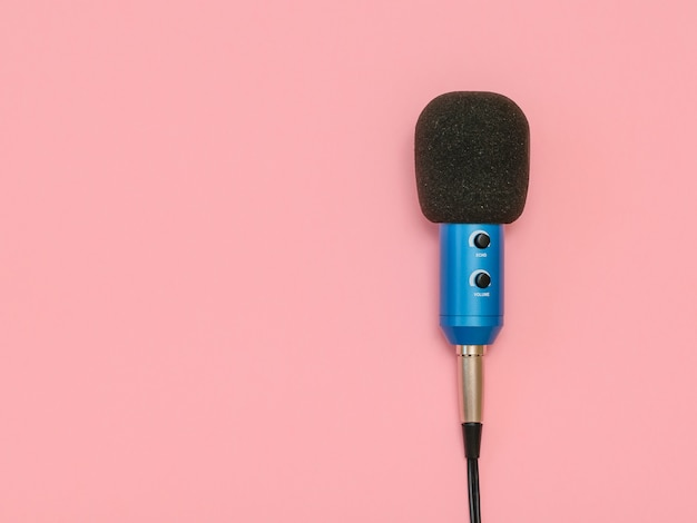 Niebieski mikrofon z drutem na różowym stole
