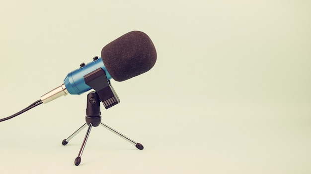 Niebieski mikrofon z przewodem na stojaku w stylu vintage. sprzęt do studia i na koncerty.