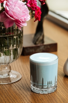 Niebieski napój latte z lawendą w szklance na stole z kwiatami