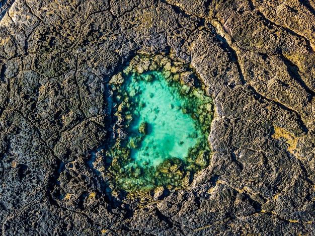Niebieski naturalny basen pośrodku czarnych skał wulkanicznych - zielona woda oceaniczna laguny - widok z góry z lotu ptaka - piękno koncepcji planety i dnia ziemi - miejsce wypoczynku letniego