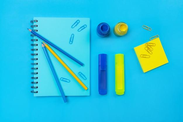 Niebieski notatnik z czarnymi kółkami z niebieskim markerem na górze z garścią spinaczy i ołówków w kolorze niebieskim i niebieskim oraz butelką farby. a materiałów biurowych. żółty i niebieski.