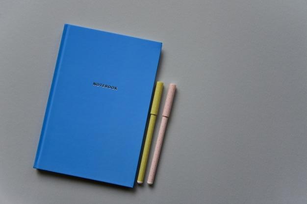 Niebieski notatnik z dwoma piórami na szarym tle papieru. widok z góry. zbliżenie. leżał na płasko.