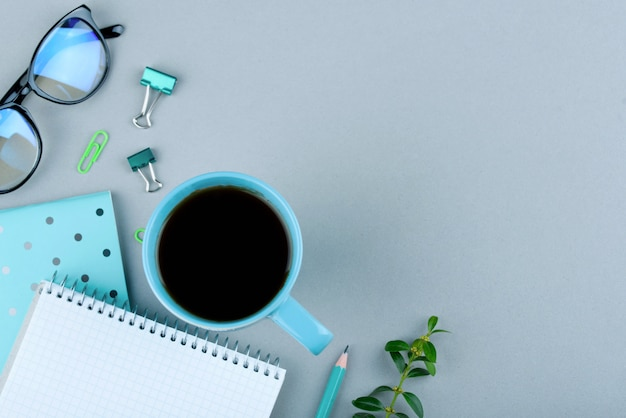 Niebieski notatnik z niebieskim ołówkiem na szaro. telefon, szklanki i filiżanka kawy.