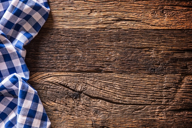 Niebieski obrus kuchenny w kratkę na rustykalnym drewnianym stole.