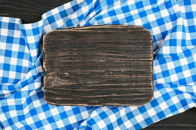 Niebieski obrus w kratkę i drewniane urządzenia do gotowania i pieczenia. tło z miejsca na kopię. poziomy.