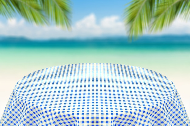 Niebieski obrus z niewyraźne tło plaży. tło dla zwykłego tekstu lub produktów