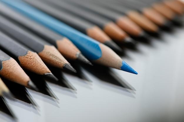 Niebieski ołówek szpieg między czarnymi ołówkami