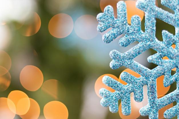 Niebieski ozdobny płatek śniegu wiszący przed choinką i jej rozmyte światła