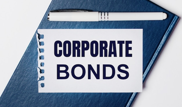 Niebieski pamiętnik leży na jasnym tle. na posiada biały długopis i kartkę z napisem obligacje korporacyjne.