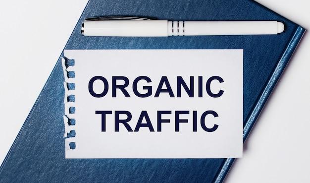 Niebieski pamiętnik leży na jasnym tle. na posiada biały długopis i kartkę z napisem organic traffic.