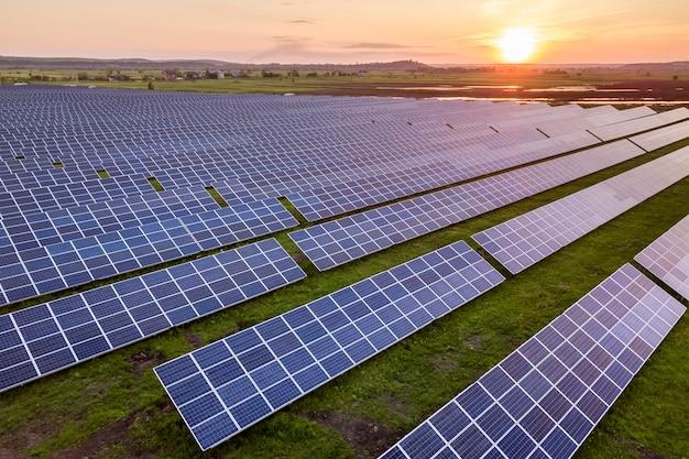 Niebieski panel słoneczny panele fotowoltaiczne wytwarzające odnawialną czystą energię na wiejskim krajobrazie i zachodzącego słońca w tle.