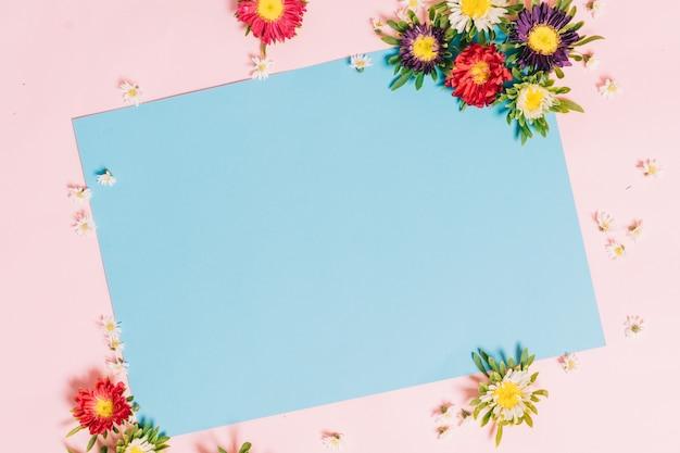 Niebieski papier jest umieszczony na różowym z kwiatami wokół