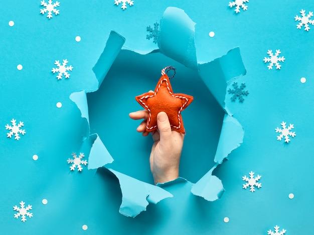 Niebieski papier leżał płasko ze płatkami śniegu i wyrwaną dziurą pośrodku. żeńska ręka trzyma czerwonej gwiazdy
