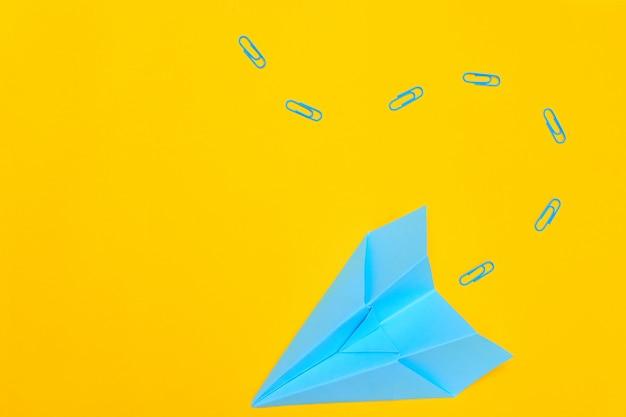 Niebieski papierowy samolot na żółtym tle