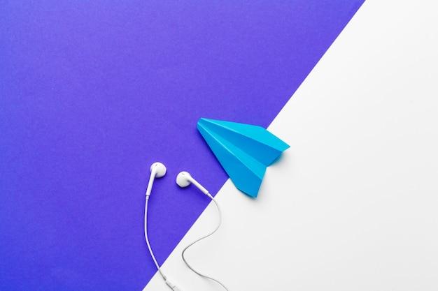 Niebieski papierowy samolot ze słuchawkami