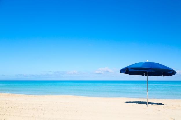 Niebieski parasol na tropikalnej plaży