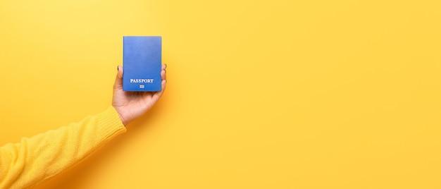 Niebieski paszport w ręku, koncepcja podróży świata