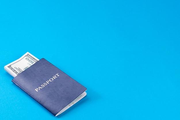 Niebieski paszport z amerykańskimi dolarami w 100 rachunkach