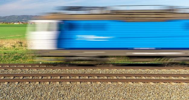 Niebieski pociąg napędzany energią elektryczną jedzie przez wieś. zamazany
