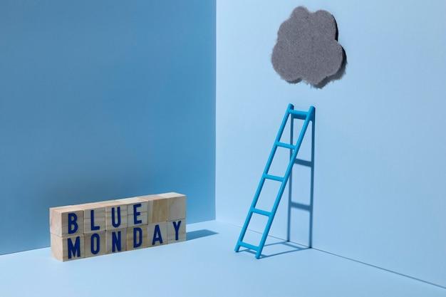 Niebieski poniedziałek z drabiną i drewnianymi kostkami