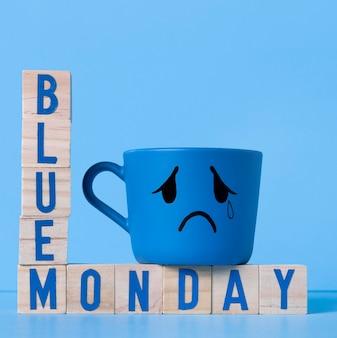 Niebieski poniedziałek z drewnianymi kostkami i płaczącym kubkiem
