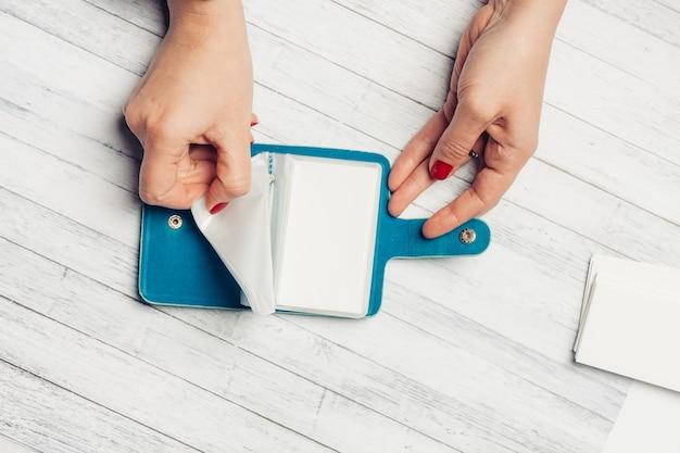 Niebieski portfel na wizytówki i drewniany stół lekcje dla kobiet jasne paznokcie