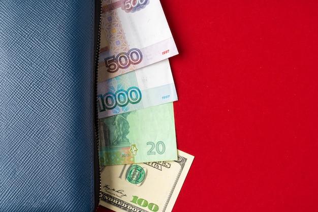 Niebieski portfel pełen pieniędzy rubli rosyjskich, dolarów amerykańskich i hrywny ukraińskiej