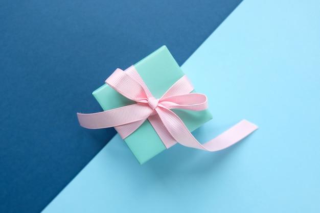 Niebieski prezent związany z różową wstążką na niebieskim tle