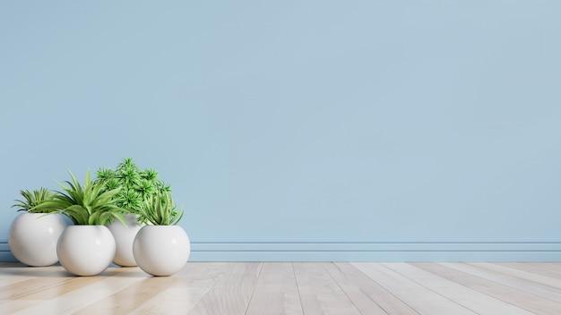 Niebieski pusty pokój z roślinami na podłodze.