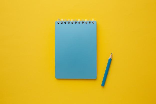 Niebieski, pusty zeszyt na twój napis z niebieskim ołówkiem na żółtym, płaskim ułożeniu