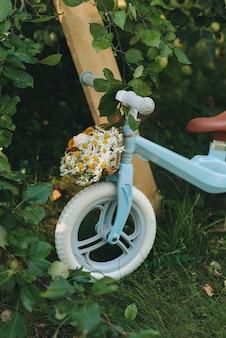 Niebieski rower dziecięcy na tle zielonego letniego ogródka.