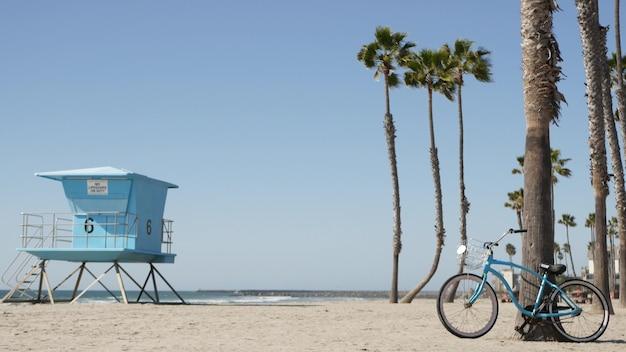 Niebieski rower, rower typu cruiser nad oceaniczną plażą, wybrzeżem morskim, palmami, wieżą ratowniczą strażnicą chaty