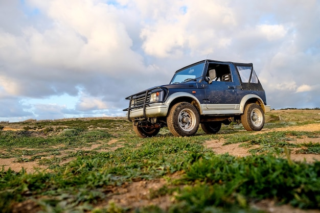 Niebieski samochód na wzgórzu porośniętym trawą w słońcu i pochmurnym niebie