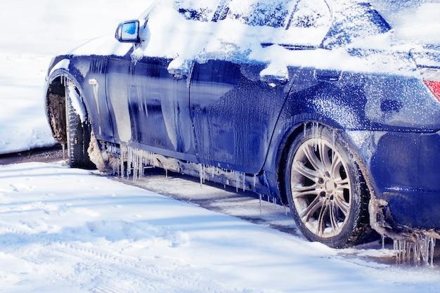 Niebieski samochód pokryty śniegiem pokryty lodem.