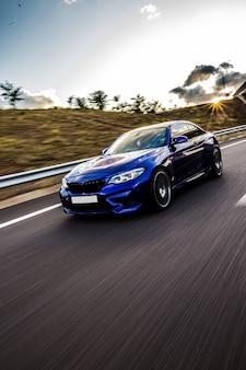 Niebieski samochód sedan jazdy na drodze w słoneczną pogodę.