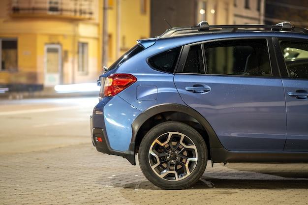 Niebieski samochód subaru crosstrek zaparkowany nocą na jasno oświetlonej ulicy miasta.