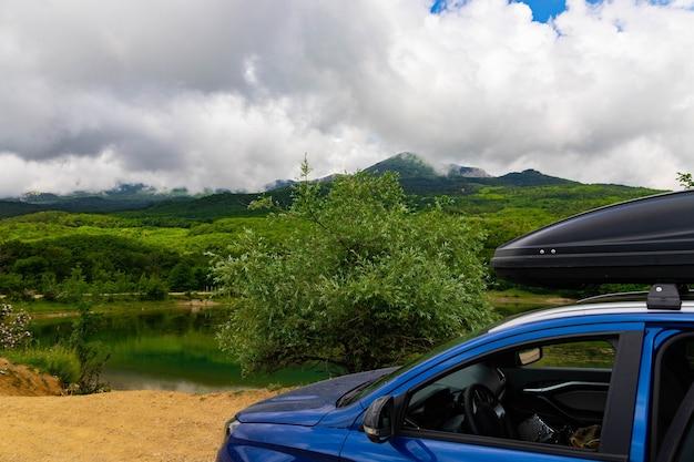 Niebieski samochód z czarnym bagażnikiem dachowym stoi na tle górskiego jeziora z górami i chmurami.