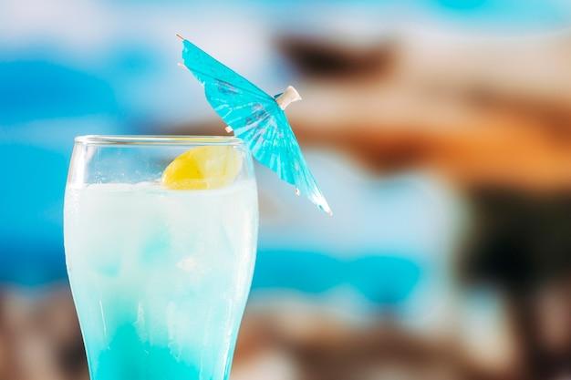 Niebieski schłodzony napój w szklance ozdobiony parasolem