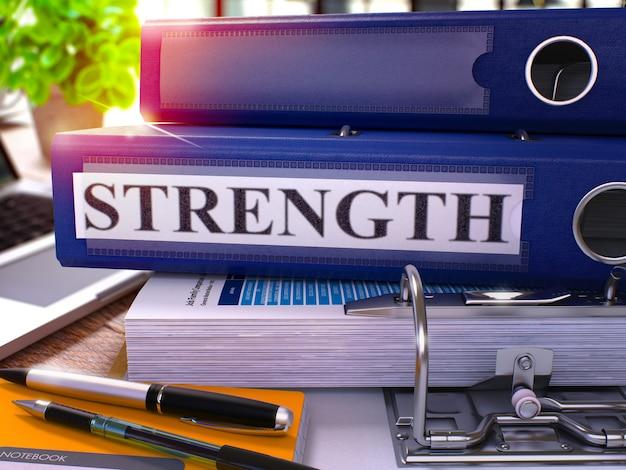 Niebieski segregator z wytrzymałością napis na tle stół roboczy z materiałów biurowych i laptopa. siła - ilustracja stonowanych. koncepcja biznesowa siła na niewyraźne tło. renderowanie 3d.