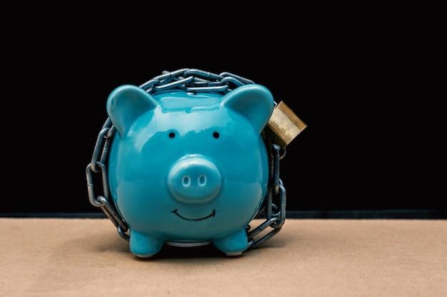 Niebieski skarbonka zablokowana, przykuta czarnym tłem, chroń oszczędności, chroń kapitał, chroń koncepcję funduszu emerytalnego.