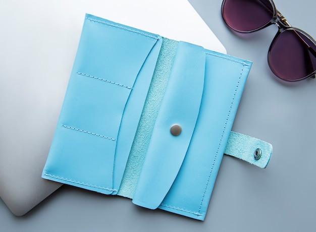 Niebieski skórzany portfel na szarej powierzchni