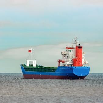 Niebieski statek towarowy wpływający na morze bałtyckie. ryga, europa