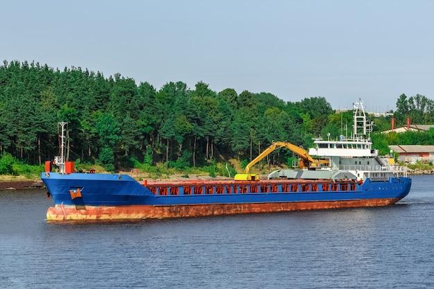 Niebieski statek towarowy z koparką o długim zasięgu przemieszcza się do portu