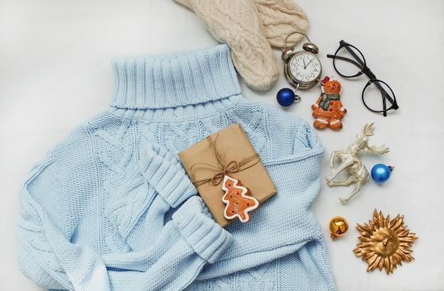 Niebieski sweter, rękawiczki z dzianiny i ozdoby świąteczne